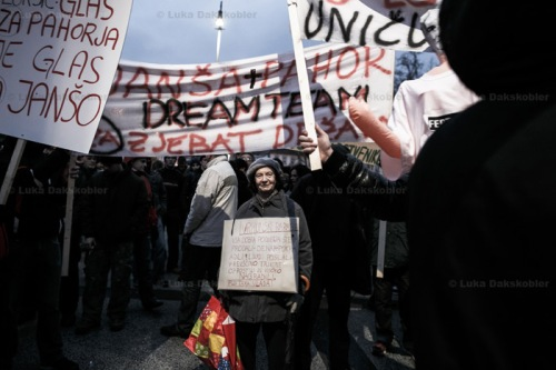 A protester carries a sign with several accusations against the government during anti-government protests in Ljubljana, Slovenia, November 30, 2012.