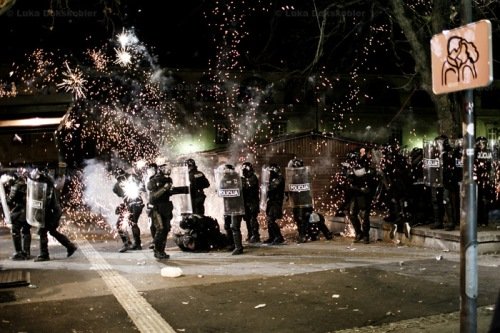 Fireworks go off in a group of policemen making an arrest during protests against the mayor of Maribor Franc Kangler in Maribor, Slovenia, on December 3, 2012.