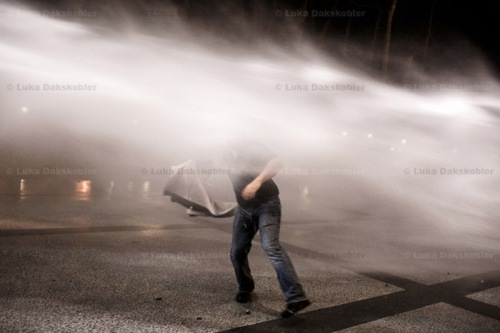 A protester tries to evade a water canon jet during anti-government protests in Ljubljana, Slovenia, on November 30, 2012. This was the first time in history of the country that the water canon was used.